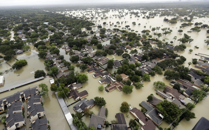 """FILE - In this Aug. 29, 2017, file photo, water from Addicks Reservoir flows into neighborhoods from floodwaters brought on by Tropical Storm Harvey in Houston. A trial has begun to determine if residents can be compensated after their homes and businesses were flooded by two reservoirs during Hurricane Harvey in 2017. The two-week trial in Houston federal court, which started Monday, is focusing on 13 flooded properties serving as test cases to determine whether the federal government would be liable for damages. Lawyers representing the federal government say flooding from a storm of Harvey's size was """"inevitable.""""(AP Photo/David J. Phillip, File)"""