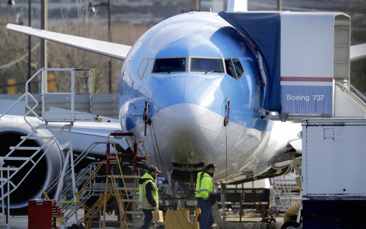 FILE - In this March 13, 2019, file photo, workers walk past a Boeing 737 MAX 8 airplane being built at Boeing Co.'s Renton Assembly Plant in Renton, Wash. Asian airlines are cutting routes, revamping their schedules and leasing extra aircraft to fill the gaps left by groundings of Boeing 737 Max 8s after deadly crashes in Indonesia and Ethiopia killed 346 people. (AP Photo/Ted S. Warren, File)