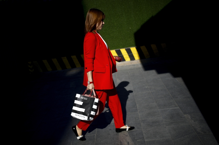 """A beam of sunlight is cast on a woman on her way to work at the Central Business District in Beijing, Tuesday, May 7, 2019. Accusing Beijing of """"reneging"""" on commitments it made in earlier talks, U.S. Trade Representative Robert Lighthizer says the Trump administration will increase tariffs on $200 billion in Chinese goods beginning Friday, a sharp escalation in a yearlong trade dispute. (AP Photo/Andy Wong)"""