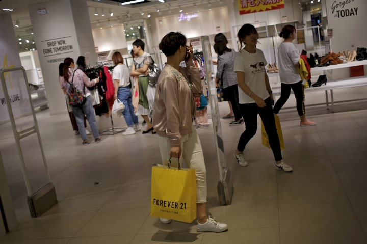 Chinese women carry paper bag of Forever 21, an American fast fashion retailer which is offering clearance discounts at a shopping mall after it pulled out from China's market, in Beijing, Tuesday, May 7, 2019. China confirmed Tuesday its economy czar will go to Washington for trade talks despite fears he might cancel after President Donald Trump threatened to escalate a tariff war over Beijing's technology ambitions. (AP Photo/Andy Wong)