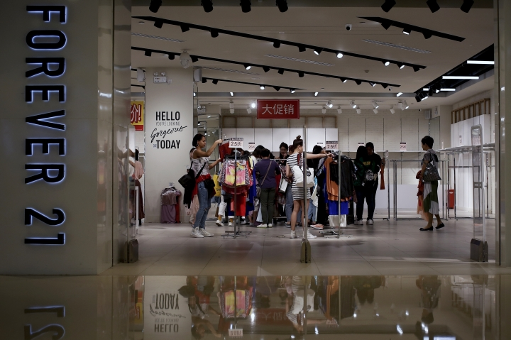 "Women select clothing at an American fast fashion retailer ""Forever 21"" which is offering clearance discounts at a shopping mall after it pulled out from China's market, in Beijing, Tuesday, May 7, 2019. China confirmed Tuesday its economy czar will go to Washington for trade talks despite fears he might cancel after President Donald Trump threatened to escalate a tariff war over Beijing's technology ambitions. (AP Photo/Andy Wong)"
