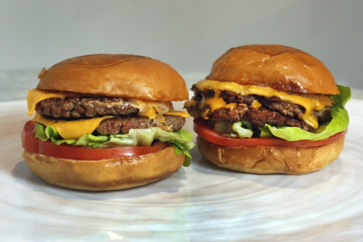 An Original Impossible Burger, left, and a Cali Burger, from Umami Burger, are shown in this photo in New York, Friday, May 3, 2019. A new era of meat alternatives is here, with Beyond Meat becoming the first vegan meat company to go public and Impossible Burger popping up on menus around the country. (AP Photo/Richard Drew)