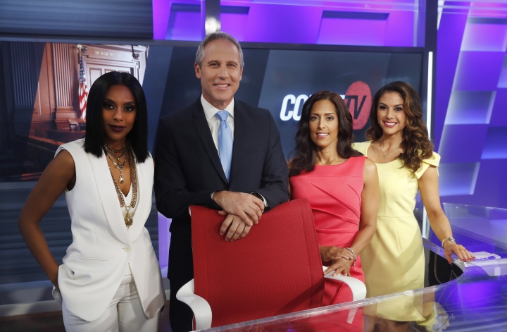In this Thursday, May 2, 2019, photo, Court TV's Yodit Tewolde, from left, Vinnie Politan, Seema Iyer and Julie Grant pose at the Court TV anchor desk, in Atlanta. (AP Photo/John Bazemore)