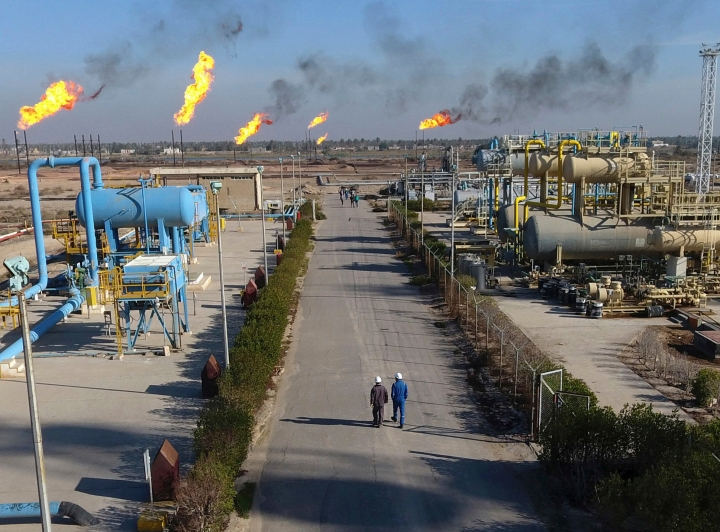 FILE - in this Thursday, Jan. 12, 2017 file photo, laborers walk in the Nihran Bin Omar field north near Basra, Iraq. Prime Minister Adel Abdul-Mahdi said Tuesday, May 7, 2019 that he has instructed Iraq's Oil Ministry to finalize an agreement with global energy giants ExxonMobil and PetroChina to lead a $53 billion megaproject to boost oil production. (AP Photo/Nabil al-Jurani, File)