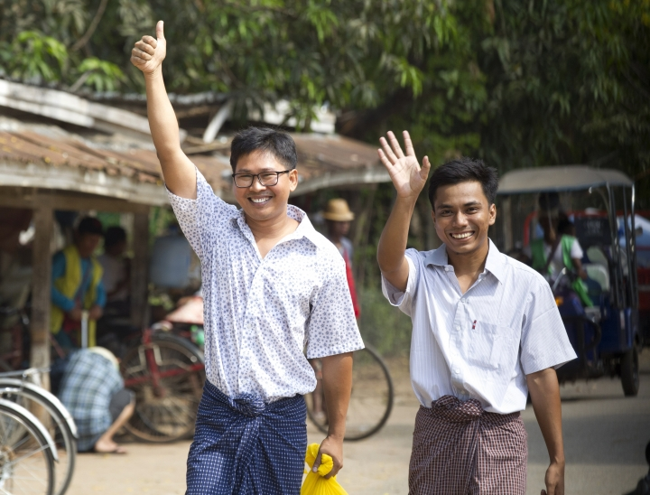 Reuters journalists Wa Lone, left, and Kyaw She Oo wave as they walk out from Insein Prison after being released in Yangon, Myanmar Tuesday, May 7, 2019. The chief of the prison said two Reuters journalists who were imprisoned for breaking the country's Officials Secrets Act have been released. (AP Photo/Thein Zaw)