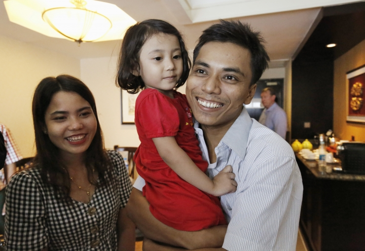 Reuters journalist Kyaw Soe Oo celebrates with wife Chit Su Win and their daughter after being released from prison after a presidential pardon, Tuesday, May 7, 2019, in Yangon, Myanmar. The two journalists Wa Lone, 32, and Kyaw Soe Oo, 28, were imprisoned for breaking Myanmar's Official Secrets Act over reporting on security forces' abuses of Rohingya Muslims were pardoned Tuesday, the prison chief and witnesses said. (Ann Wang/Pool Photo via AP)
