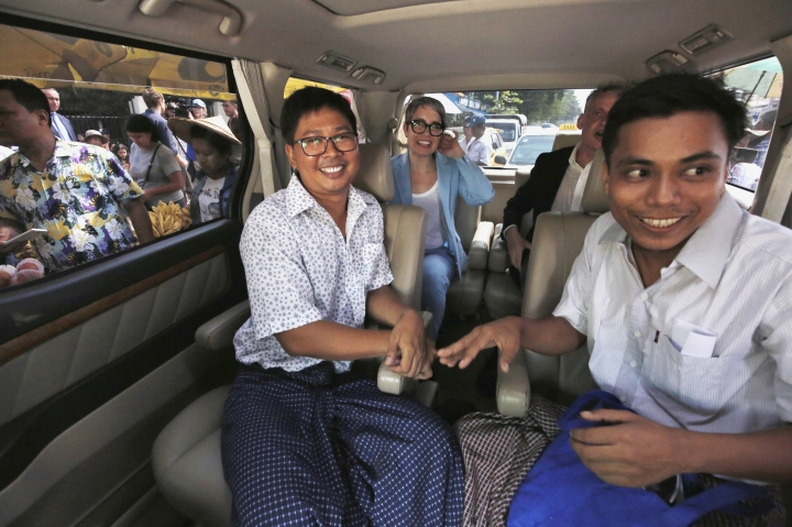 Reuters reporters Wa Lone, front left, and Kyaw Soe Oo, front right, sit in a vehicle after being freed from Insein Prison in Yangon, Myanmar, Tuesday, May 7, 2019. Two Reuters journalists who were imprisoned for breaking Myanmar's Official Secrets Act over reporting on security forces' abuses of Rohingya Muslims were pardoned and released Tuesday, the prison chief and witnesses said. (Ann Wang/Pool Photo via AP)