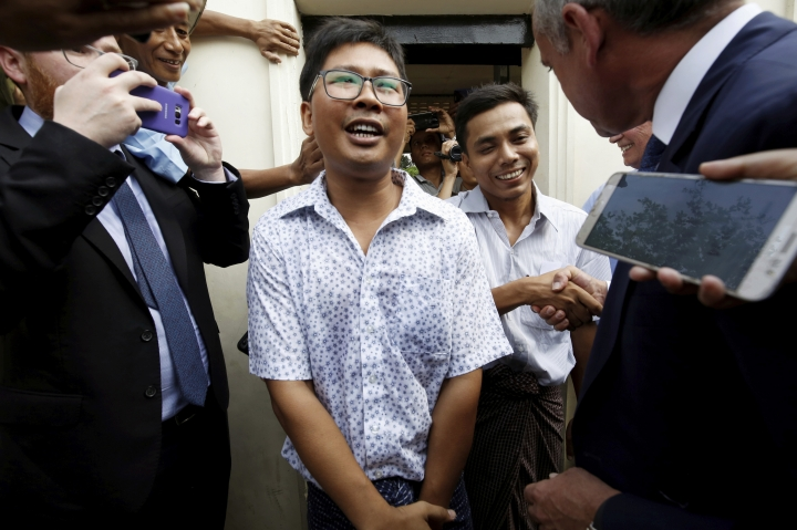 Reuters reporters Wa Lone, front center, and Kyaw Soe Oo, rear center, react as they are freed from Insein Prison in Yangon, Myanmar, Tuesday, May 7, 2019. Two Reuters journalists who were imprisoned for breaking Myanmar's Official Secrets Act over reporting on security forces' abuses of Rohingya Muslims were pardoned and released Tuesday, the prison chief and witnesses said. (Ann Wang/Pool Photo via AP)