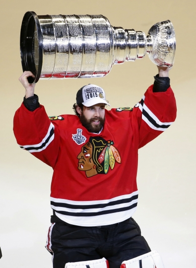 FILE - In this June 10, 2015, file photo, Chicago Blackhawks' goalie Corey Crawford hoists the Stanley Cup trophy after defeating the Tampa Bay Lightning in Game 6 of the NHL hockey Stanley Cup Final series, in Chicago. Two-time Stanley Cup champion goaltender Corey Crawford will drive the pace car for Saturday's IndyCar Grand Prix. Race organizers said Tuesday, May 7, 2019, that Crawford will drive a Chevrolet Corvette Grand Sport Coupe on Indianapolis Motor Speedway's 14-turn, 2.439-mile road course. (AP Photo/Charles Rex Arbogast, File)