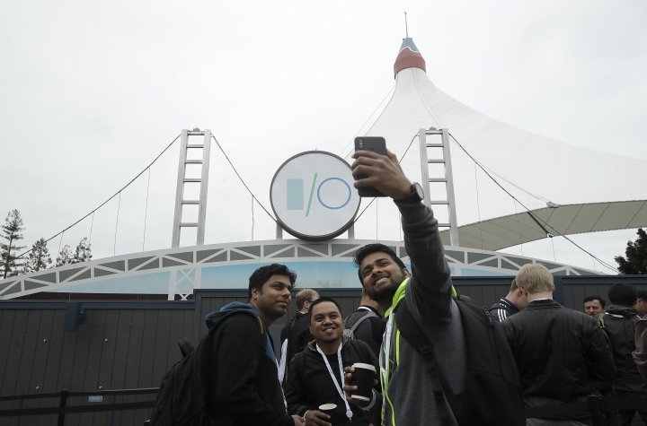 A group of attendees take photos while waiting in line for the keynote address of the Google I/O conference in Mountain View, Calif., Tuesday, May 7, 2019. (AP Photo/Jeff Chiu)
