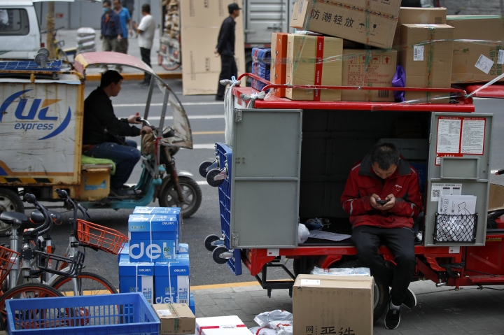 A private delivery company's courier sits on his delivery cart sorting boxes of goods for his customers outside an office building at the Central Business District in Beijing, Wednesday, May 8, 2019. Washington and Beijing have raised tariffs on billions of dollars of each other's exports, disrupting trade in goods from soybeans to medical equipment. Estimates of lost potential sales so far range as high as $25 billion. (AP Photo/Andy Wong)