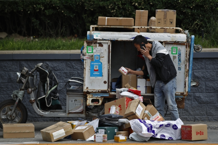 A private delivery company's courier sorts boxes of goods for his customers at the Central Business District in Beijing, Wednesday, May 8, 2019. Washington and Beijing have raised tariffs on billions of dollars of each other's exports, disrupting trade in goods from soybeans to medical equipment. Estimates of lost potential sales so far range as high as $25 billion.(AP Photo/Andy Wong)