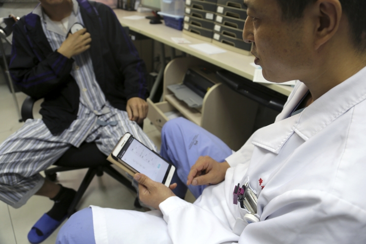 Dr. Li Dianyou uses a tablet computer to adjust the settings of a deep brain stimulation device implanted in the brain of a methamphetamine addict named Yan, left, on Monday, Oct. 29, 2018, at Ruijin Hospital in Shanghai, China. Western attempts to push forward with human trials of DBS for drug addiction have foundered, even as China has emerged as a hub for this kind of research. But the vast suffering wrought by the U.S. opioid epidemic may be changing the risk-reward calculus. Now, the experimental surgery Yan underwent is coming to America. (AP Photo/Erika Kinetz)