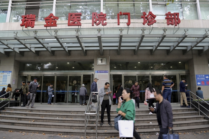 People walk past an entrance to Ruijin Hospital on Thursday, Oct. 25, 2018, in Shanghai, China. Doctors at Ruijin have tried to turn the hospital into a center of deep brain stimulation research. The hope is that the technology will heal a host of conditions, including addiction, with the flip of a switch. Western attempts to push forward with human trials of DBS for addiction have foundered, even as China emerged as a hub for this kind of research. (AP Photo/Erika Kinetz)