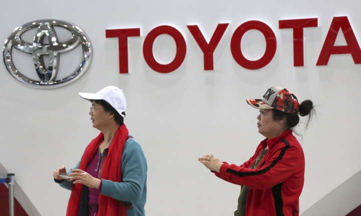 Visitors walk through a Toyota showroom in Tokyo, Wednesday, May 8, 2019. Japan's top automaker Toyota is reporting a 4% dip in profit for January-March after vehicle sales fell in North America. (AP Photo/Koji Sasahara)