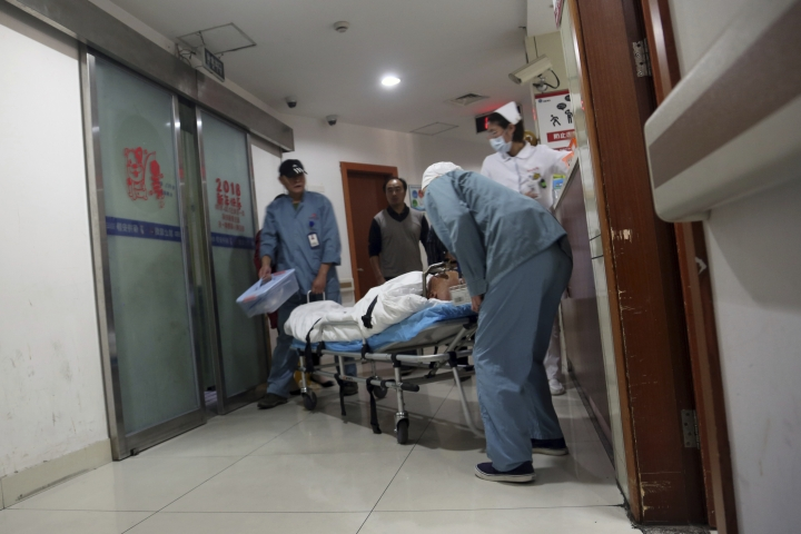 Orderlies roll a brain surgery patient out of the functional neurosurgery center at Ruijin Hospital in Shanghai, China on Monday, Oct. 29, 2018. Doctors at Ruijin are experimenting with deep brain stimulation as a treatment for addiction. The hope is that the technology will extinguish addiction, quite literally, with the flip of a switch. Critics say such experiments are premature and risky, but U.S. regulators in February greenlighted a human trial of DBS for opioid addiction at West Virginia University. (AP Photo/Erika Kinetz)