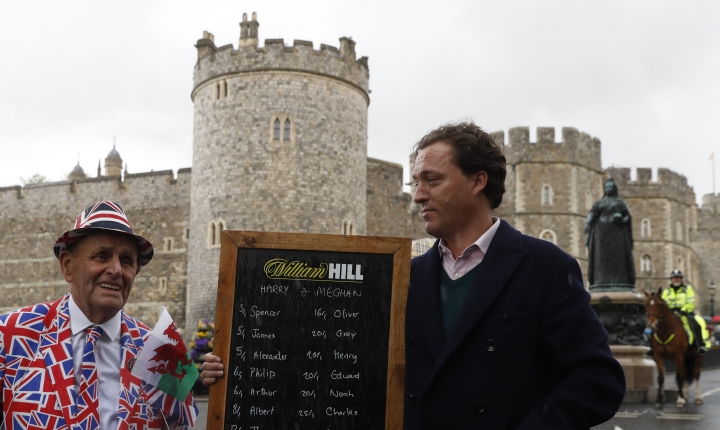 Royal fan Terry Hutt, left, poses with Rupert Adams from the British bookmaker William Hill showing a list for the odds on names for the yet unnamed baby son of Prince Harry and Meghan, Duchess of Sussex outside Windsor Castle, in Windsor, England Wednesday, May 8, 2019. Meghan gave birth to the boy on Monday. (AP Photo/Alastair Grant)