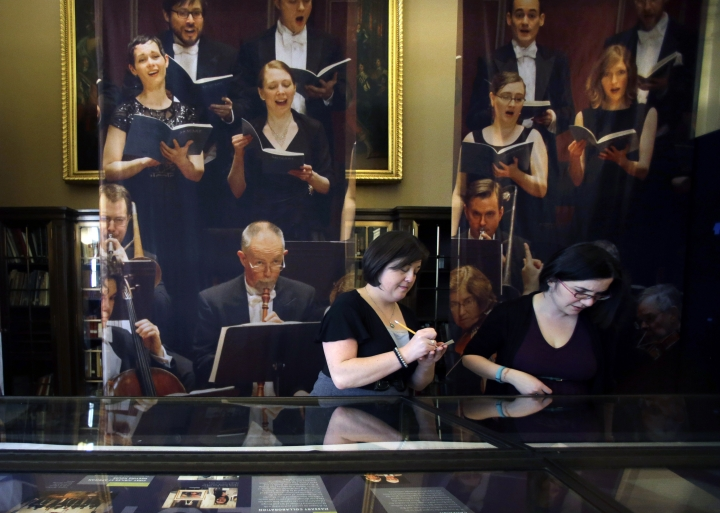 "FILE - In this March 20, 2015. file photo, archivist Michelle Chiles, left, and exhibition developer Tamar Agulian help set up the Handel & Haydn Society bicentennial exhibit at the Boston Public Library in Boston. On Sunday, May 5, 2019, the Handel & Haydn Society was finishing a rendition of Mozart's ""Masonic Funeral"" at Boston's Symphony Hall when a youngster blurted out loudly: ""WOW!"" The organization has mounted a search for the kid it's calling the ""Wow Child"" — not to reprimand, but to offer a chance to meet the conductor. (AP Photo/Elise Amendola, File)"