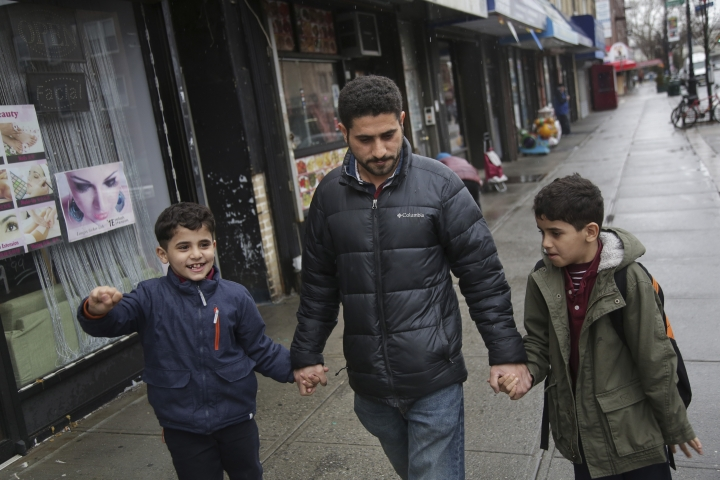 In this March 21, 2019, photo, Sadek Ahmed walks with his sons Adel, 9, right, and Mutaz, 7, after picking them up from school in the Brooklyn borough of New York. Their mother, Amena Abdulkarem, is stuck in Yemen with her two younger sons, the boys' brothers. Their family's situation is representative of the toll that the Trump administration's almost-forgotten travel ban has taken on an untold number of families. (AP Photo/Seth Wenig)