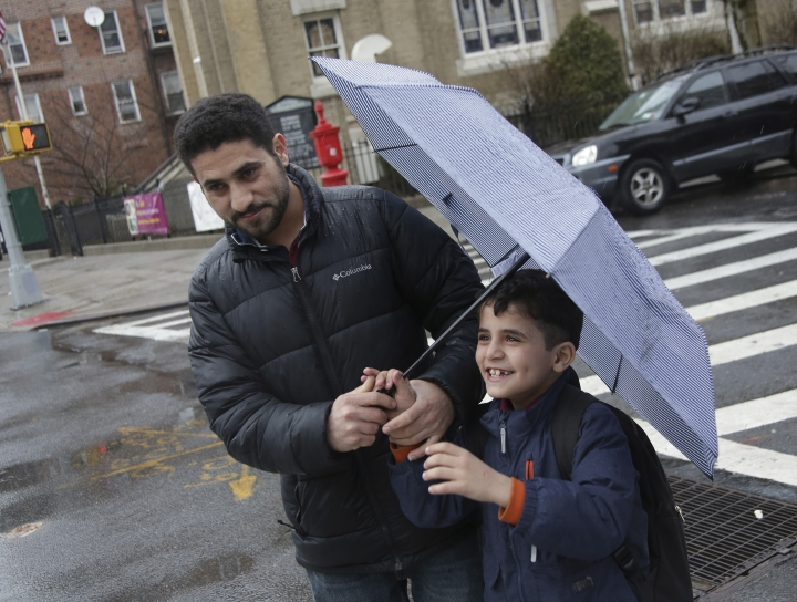 In this Thursday, March 21, 2019, photo, Sadek Ahmed walks with his son Mutaz, 7, after picking him up from school in the Brooklyn borough of New York. The Trump administration's travel ban has forced American citizens to live apart from their husbands, wives and children for years, and there's no end in sight for many families. (AP Photo/Seth Wenig)