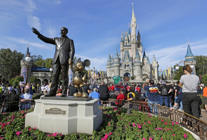 FILE - In this Jan. 9, 2019 photo, guests watch a show near a statue of Walt Disney and Micky Mouse in front of the Cinderella Castle at the Magic Kingdom at Walt Disney World in Lake Buena Vista, Fla. The Walt Disney Company reports financial results Wednesday, May 8. (AP Photo/John Raoux)