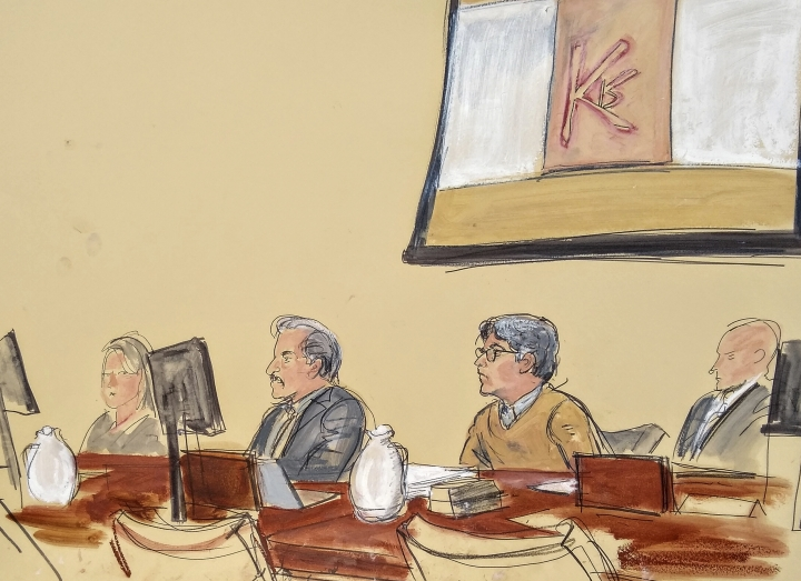 """In this courtroom artist's sketch, Keith Raniere, second from right, leader of the secretive group NXIVM, attends his trial in Brooklyn federal court, Tuesday, May 7, 2019 in New York. Above him is a screen with an image of a branding, containing his initials KR. A federal prosecutor says the self-help guru used threats, """"shame and humiliation"""" while grooming women for sex. She also described how some female followers were branded with Raniere's initials. (Elizabeth Williams via AP)"""