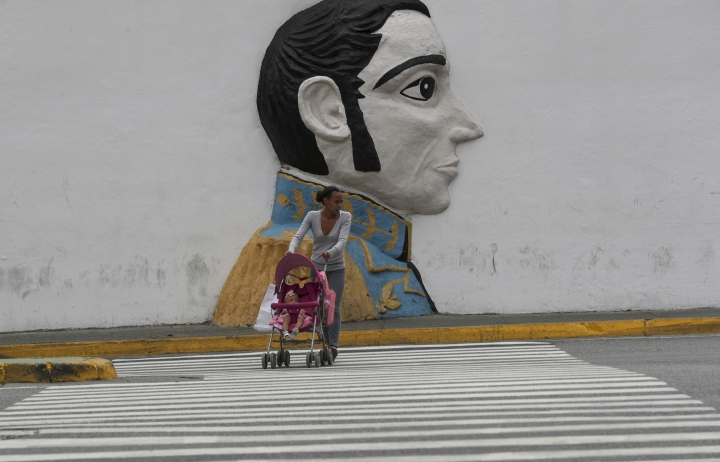 "A pedestrian looks to cross an avenue backdropped by a wall relief of Venezuelan hero Simon Bolivar, just outside of the Supreme Court building, in Caracas, Venezuela, Wednesday, May 8, 2019. Supreme Court Justice Moreno spoke Wednesday following U.S. Vice President Mike Pence's remarks that the U.S. would extend sanctions to all members of the Venezuelan court if they continue to be a ""political tool"" of President Nicolás Maduro. (AP Photo/Martin Mejia)"