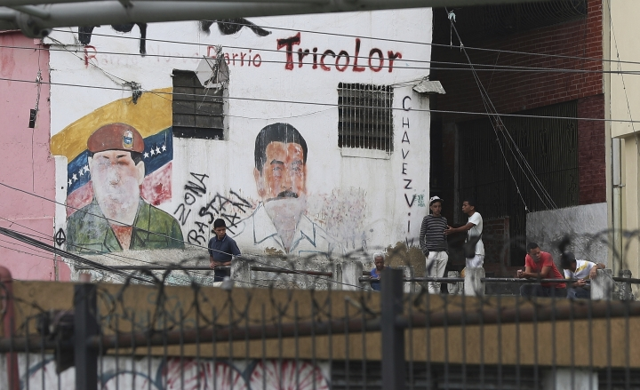 Youth hang out next to a mural featuring the late President Hugo Chavez and his successor Nicolas Madro, at the Petare shantytown, in Caracas, Venezuela, Wednesday, May 8, 2019. Venezuela has been in sharp decline for years, suffering from hyperinflation and shortages of food and medicine. (AP Photo/Martin Mejia)