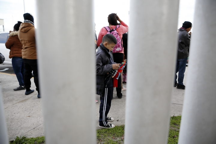FILE - In this Jan. 29, 2019 file photo, a migrant family waits with others before being transported by Mexican authorities to the San Ysidro port of entry to begin the process of applying for asylum in the United States, in Tijuana, Mexico. People in overextended Mexican border cities voiced concern over their government's silence about a U.S. policy that will continue making Central American migrants seeking asylum in the United States wait south of the border, after a U.S. federal appeals court ruled Tuesday, May 8, that the Trump administration can make migrants wait in Mexico for their immigration hearings while the policy is challenged in court. (AP Photo/Gregory Bull, File)