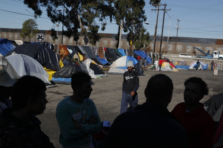 FILE - In this Dec. 7, 2018 file photo, men discuss rumors of other migrants who successfully snuck into the U.S. in a tent camp outside the closed Benito Juarez sports complex, in Tijuana, Mexico. People in overextended Mexican border cities voiced concern over their government's silence about a U.S. policy that will continue making Central American migrants seeking asylum in the United States wait south of the border, after a U.S. federal appeals court ruled Tuesday, May 8, that the Trump administration can make migrants wait in Mexico for their immigration hearings while the policy is challenged in court. (AP Photo/Rebecca Blackwell, File)