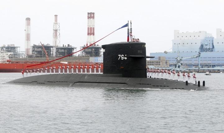 Taiwan navy sailors salute from a Dutch Zwaardvis-class submarine during a groundbreaking ceremony for the island's submarine factory in Kaohsiung, southern Taiwan, Thursday, May 9, 2019. (AP Photo/Chiang Ying-ying)