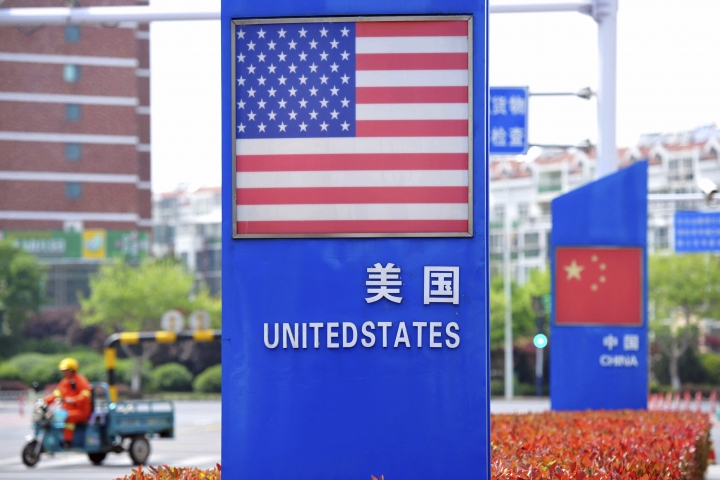 In this Wednesday, May 8, 2019, photo, a worker drives an electric cart past a display featuring the U.S. and Chinese flags in a special trade zone in Qingdao in eastern China's Shandong province. China said Thursday it will retaliate if President Donald Trump goes ahead with more tariff hikes in a fight over technology and trade, ratcheting up tensions ahead of negotiations in Washington. (Chinatopix via AP)