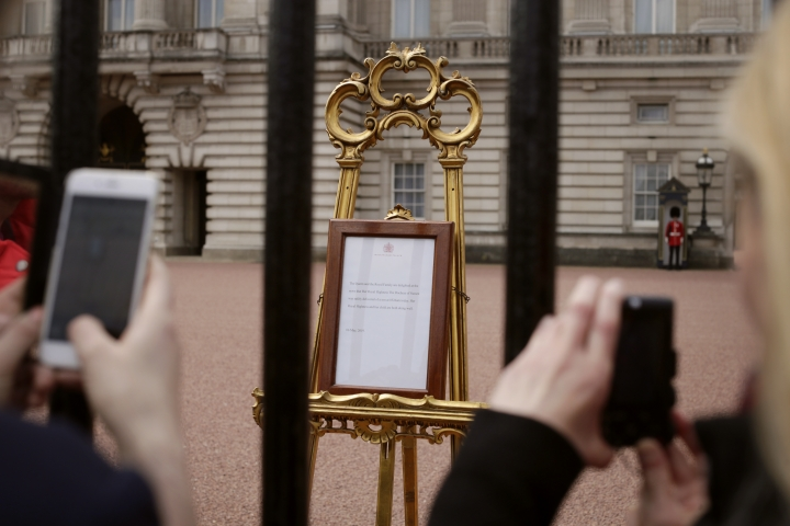 People take pictures of the notice on an easel in the forecourt of Buckingham Palace, London, Tuesday, May 7, 2019, placed on Monday to formally announce the birth of a baby boy to Britain's Prince Harry and Meghan, Duchess of Sussex. The as-yet-unnamed baby arrived less than a year after Prince Harry wed Meghan Markle in a spectacular televised event on the grounds of Windsor Castle that was watched the world over. (AP Photo/Tim Ireland)