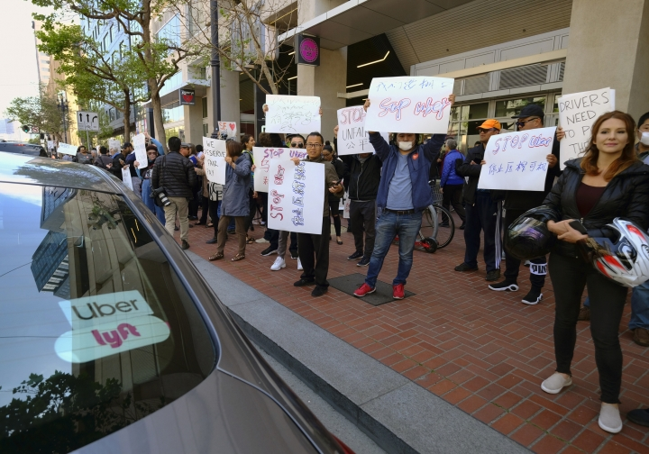 Uber and Lyft drivers carry signs during a demonstration outside of Uber headquarters Wednesday, May 8, 2019, in San Francisco. As Uber executives lure investors to infuse the company with billions of dollars ahead of the largest technology IPO this year, the men and women behind the wheels of the largest ride-hailing companies are pushing for higher wages and recognition for their role in building the companies. (AP Photo/Eric Risberg)