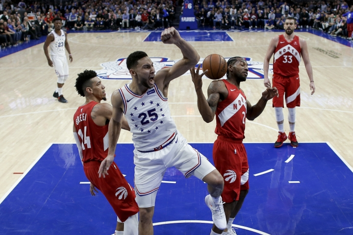 Philadelphia 76ers' Ben Simmons (25) reacts after dunking the ball between Toronto Raptors' Danny Green (14) and Kawhi Leonard (2) during the second half of Game 6 of a second-round NBA basketball playoff series Thursday, May 9, 2019, in Philadelphia. (AP Photo/Chris Szagola)