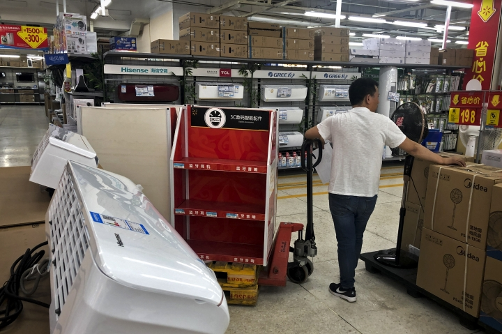 A worker with a cart loaded with shelves for digital accessories cools off in front of a fan at a section selling Chinese-made electric appliances at a hypermarket in Beijing, Thursday, May 9, 2019. Ratcheting up tension ahead of talks in Washington, China vowed Thursday to defend its own interests and retaliate if President Donald Trump goes ahead with more tariff hikes in a dispute over trade and technology. (AP Photo/Andy Wong)