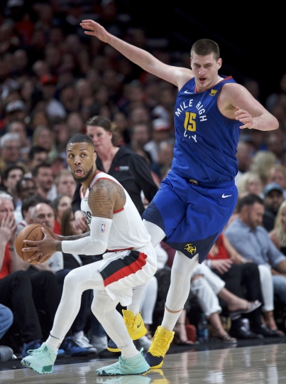 Portland Trail Blazers guard Damian Lillard, left, spins around Denver Nuggets center Nikola Jokic during the first half of Game 6 of an NBA basketball second-round playoff series Thursday, May 9, 2019, in Portland, Ore. (AP Photo/Craig Mitchelldyer)