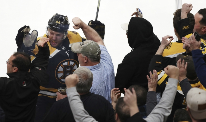 Boston Bruins' Steven Kampfer (44) leaps against the glass as he celebrates his goal against Carolina Hurricanes goaltender Petr Mrazek with fans during the first period in Game 1 of the NHL hockey Stanley Cup Eastern Conference finals Thursday, May 9, 2019, in Boston. (AP Photo/Charles Krupa)