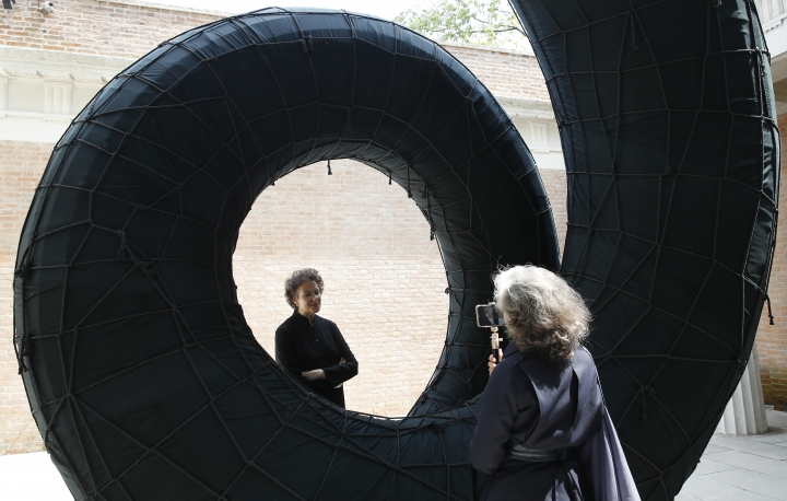 """United States curator Brooke Kamin Rapaport, left, poses for a picture at the """"Liberty"""" installation by artist Martin Puryear at the United States' pavilion during the 58th Biennale of Arts exhibition in Venice, Italy, Tuesday, May 7, 2019. Political issues that excite newsprint, airwaves and social media, such as fake news, migration, poverty, global warming and armed conflict, are getting a very open airing at the 58th Venice Biennale contemporary art fair, which Saturday, May 11, and runs through Nov. 24, 2019. (AP Photo/Antonio Calanni)"""