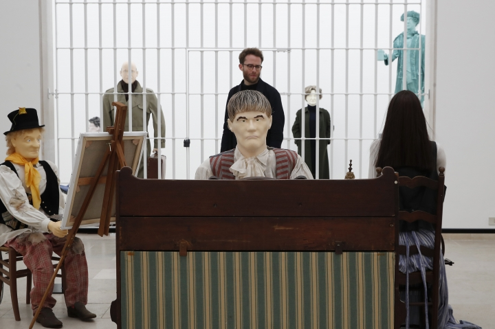 """A man looks the """"Mondo Cane"""" installation by artists Jos de Gruyter & Harald Thys shown at Belgium's pavilion during the 58th Biennale of Arts exhibition in Venice, Italy, Tuesday, May 7, 2019. Political issues that excite newsprint, airwaves and social media, such as fake news, migration, poverty, global warming and armed conflict, are getting a very open airing at the 58th Venice Biennale contemporary art fair, which Saturday, May 11, and runs through Nov. 24, 2019. (AP Photo/Antonio Calanni)"""