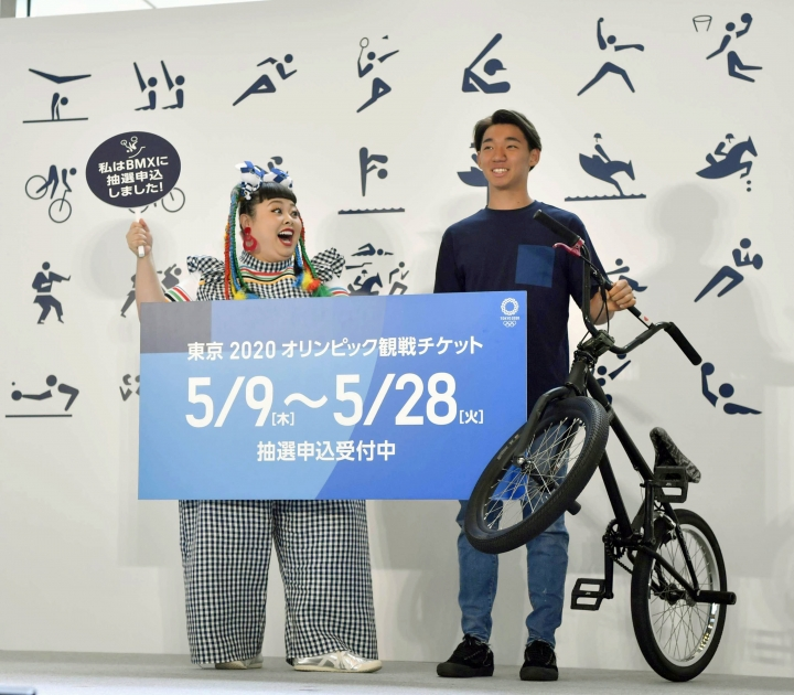 "Japanese comedian Naomi Watanabe, left, and BMX rider Rimu Nakamura attend an event to mark the start of application to buy tickets for the 2020 Tokyo Olympic Games, in Tokyo Thursday, May 8, 2019. Japan residents began Thursday entering a lottery system, hoping to land tickets for next year's Tokyo Olympics. The sign reads "" Tickets for the 2020 Tokyo Olympic Games. Open for entering a lottery system."" (Yu Nakajima/Kyodo News via AP)"
