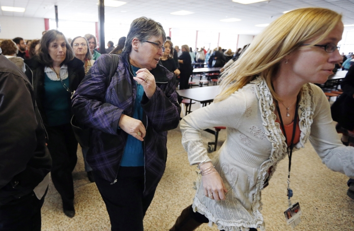 FILE - In this March 15, 2013, file photo, participants rush out of the cafeteria after hearing gun shots during a lockdown exercise at Milford High School in Milford, Mass. The actions of students who died tackling gunmen at two separate U.S. campuses a week apart have been hailed as heroic. At a growing number of schools around the country, they also reflect guidance to students who are told, at least in some situations, to do what they can to disrupt shootings. (AP Photo/Michael Dwyer, File)