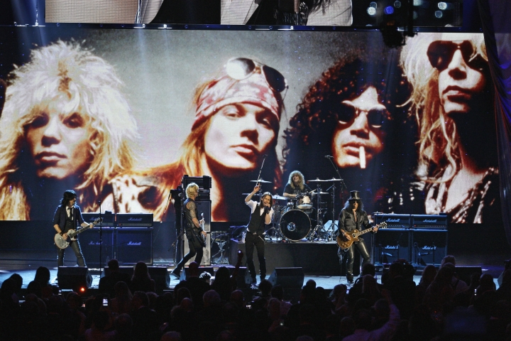 FILE - In this April 15, 2012, file photo, Guns N' Roses performs with singer Myles Kennedy after their induction into the Rock and Roll Hall of Fame in Cleveland. The rock band is accusing a Colorado brewery of stealing their brand and piggybacking off their fame to sell beer and merchandise. The band filed a trademark infringement lawsuit Thursday, May 9, 2019, against Colorado-based Oskar Blues Brewery, which sells Guns 'N' Rosé beer and merchandise, including bandannas the group says is uniquely associated with singer Axl Rose. (AP Photo/Tony Dejak, File)