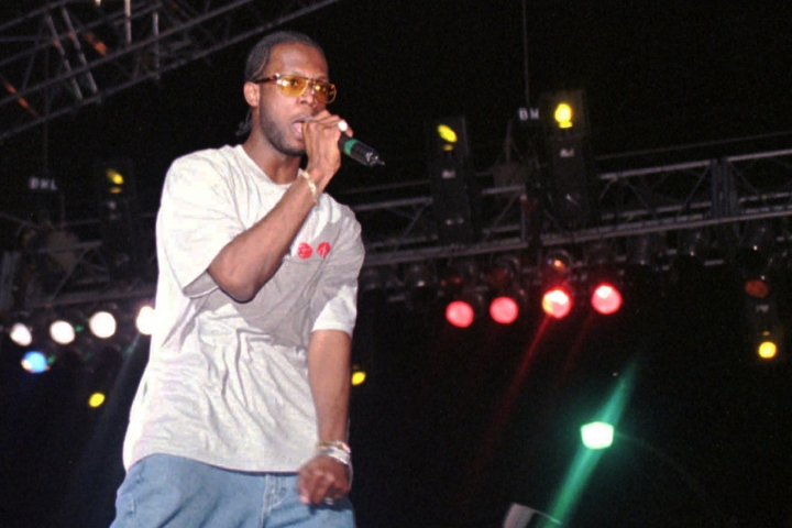 "FILE - In this April 12, 1997, file photo, Prakazrel ""Pras"" Michel, part of the group the Fugees, sings on stage during a concert in Port-au-Prince, Haiti. A lawyer for one of the founding members of the 1990s hip hop group the Fugees says his client is facing charges related to 2012 campaign contributions. Defense lawyer Barry Pollack said Friday, May 10, 2019, that Michel is innocent and looks forward to having the case heard by a jury.(AP Photo/Daniel Morel, File)"