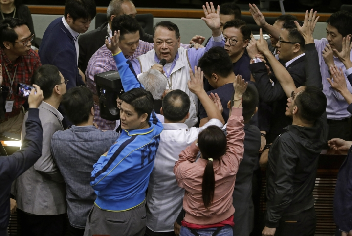 Pro-Beijing lawmaker Shek Lai-him, center, is surrounded by both pro-democracy and pro Beijing lawmakers during a controversial amendments meeting at Legislative Council in Hong Kong, Saturday, May 11, 2019. Hong Kong's legislative assembly descended into chaos Saturday as lawmakers for and against controversial amendments to the territory's extradition law clashed over access to the chamber. (AP Photo/Vincent Yu)