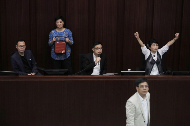 Pro-democracy lawmaker James To, center, speaks in the chamber at Legislative Council in Hong Kong, Saturday, May 11, 2019. Hong Kong's legislative assembly descended into chaos Saturday as lawmakers for and against controversial amendments to the territory's extradition law clashed over access to the chamber. (AP Photo/Kin Cheung)