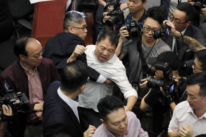 Pro-democracy lawmaker Wu Chi-wai, center, scuffles with security guards at Legislative Council in Hong Kong, Saturday, May 11, 2019. Hong Kong's legislative assembly descended into chaos Saturday as lawmakers for and against controversial amendments to the territory's extradition law clashed over access to the chamber. (AP Photo/Kin Cheung)