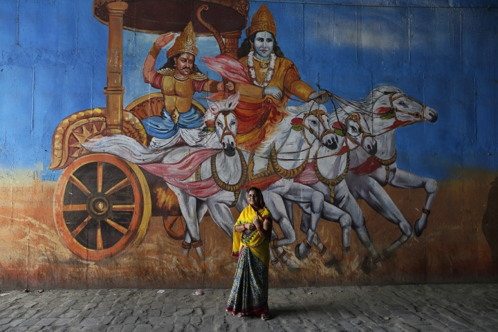 An Indian woman displays indelible mark on her finger after casting vote standing next to a mural depicting a scene from the Hindu epic Mahabharata in Prayagraj, Uttar Pradesh state, India , Sunday, May 12, 2019. Indians are voting in the next-to-last round of 6-week-long national elections, marked by a highly acrimonious campaign with Prime Minister Narendra Modi flaying the opposition Congress party rival Rahul Gandhi's family for the country's ills. (AP Photo/Rajesh Kumar Singh)