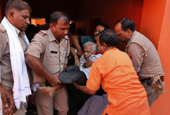Ganesh Prasad, a 74 year old who fell unconscious while waiting in queue to cast his vote is carried away in Prayagraj, Uttar Pradesh state, India , Sunday, May 12, 2019. Indians are voting in the next-to-last round of 6-week-long national elections, marked by a highly acrimonious campaign with Prime Minister Narendra Modi flaying the opposition Congress party rival Rahul Gandhi's family for the country's ills. (AP Photo/Rajesh Kumar Singh)