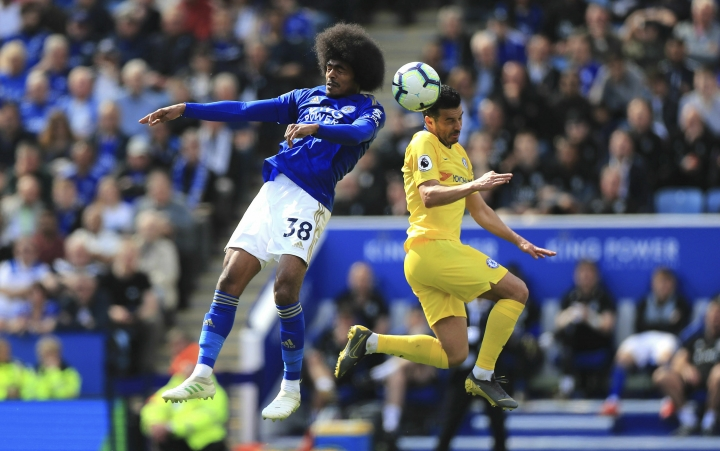Leicester City's Hamza Choudhury, left, and Chelsea's Pedro battle for the ball in the air during their English Premier League soccer match at the King Power Stadium, Leicester, England, Sunday, May 12, 2019. (Mike Egerton/PA via AP)